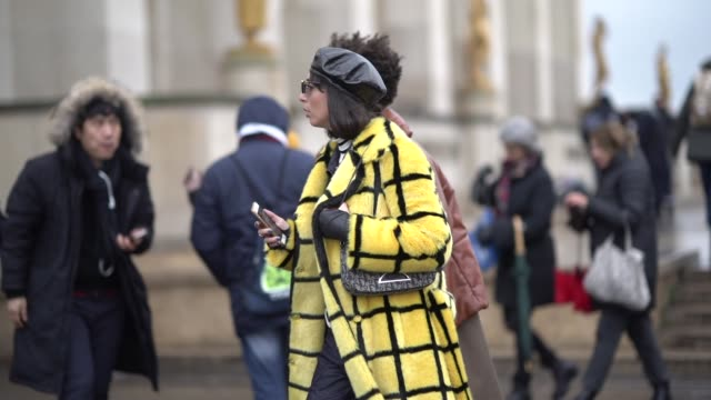A guest wears a black beret hat a yellow checked fluffy coat a Dior bag shoes outside Elie Saab during Paris Fashion Week Haute Couture Spring Summer...