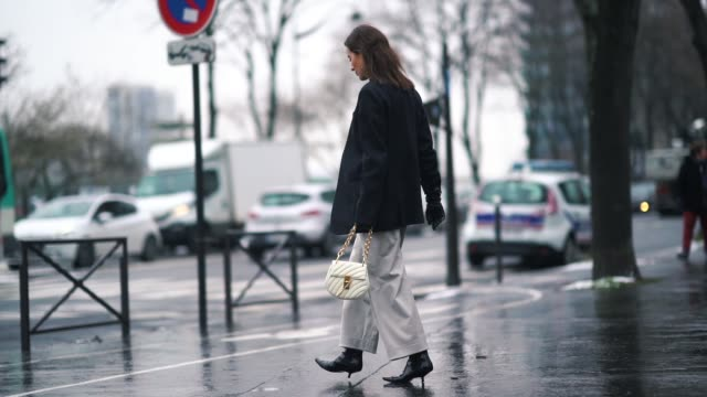 stockvideo's en b-roll-footage met a guest wears a black blazer jacket white flare pants a white bag a black turtleneck during paris fashion week womenswear fall/winter 2018/2019 on... - coltrui