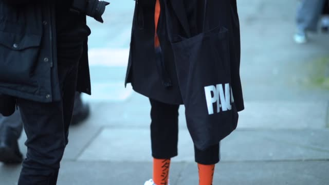 A guest wears a black coat orange socks white sneakers during London Fashion Week Men's January 2018 at on January 06 2018 in London England