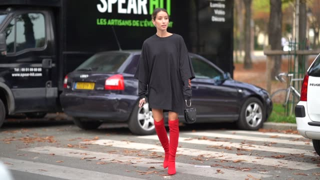 A guest wears a black dress a black bag red thigh high boots outside the Rochas show during Paris Fashion Week Womenswear Spring/Summer 2018 on...