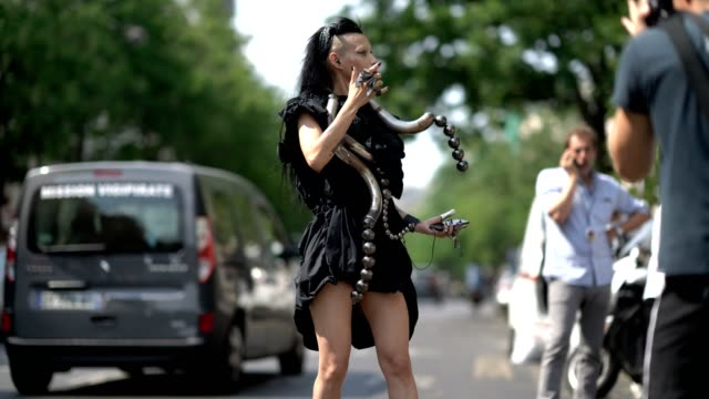 guest wears a black dress, a large necklace made of metal representing a snake, and black heels, outside the y/project show, during paris fashion... - black dress stock videos & royalty-free footage