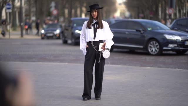 vídeos y material grabado en eventos de stock de guest wears a black hat, a white shirt, black flare pants , outside chanel, during paris fashion week womenswear fall/winter 2018/2019, on march 6,... - camiseta