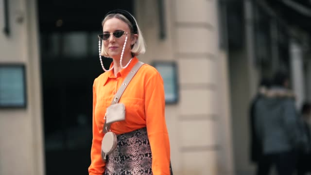 guest wears a black headband, sunglasses, a beige crossbody strap with three small bags, an orange shirt, a beige python pattern long skirt, a beige... - street style stock videos & royalty-free footage