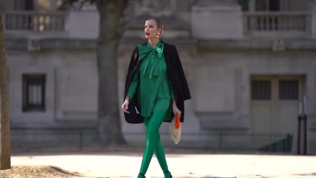 guest wears a black jacket, green leggings, a ruffled top, earrings, outside elie saab, during paris fashion week womenswear spring/summer 2019, on... - orecchini video stock e b–roll