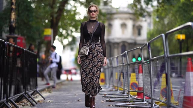 guest wears a black lace mesh top, a floral print skirt, brown leather boots, a snake print bag, during london fashion week september 2018 on... - mesh textile stock videos & royalty-free footage