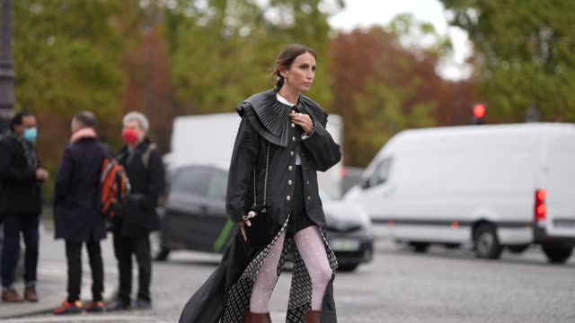 guest wears a black long dress with large shiny ruffled collar, white leggings, black and brown leather boots, outside chanel, during paris fashion... - leggings stock videos & royalty-free footage