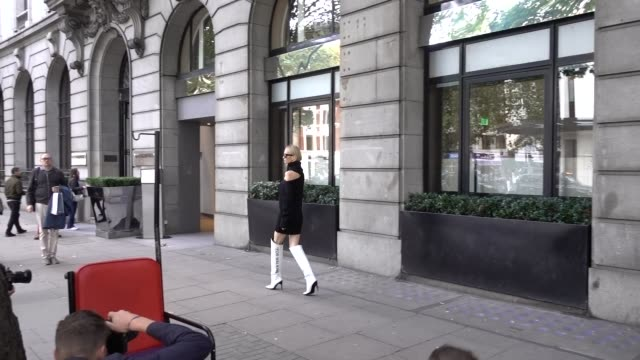 guest wears a black off shoulder top, silver sunglasses, white leather thigh high boots with the printed inscription 'for walking', outside peter... - thigh stock videos & royalty-free footage
