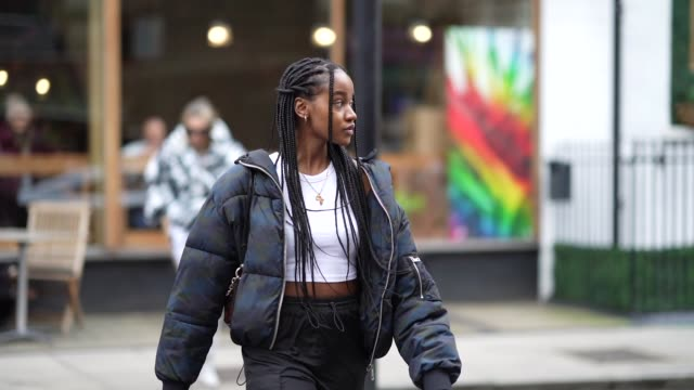 a guest wears a black oversized puffer jacket a white cropped tshirt a necklace a bag earrings during london fashion week february 2020 on february... - zöpfchenfrisur stock-videos und b-roll-filmmaterial