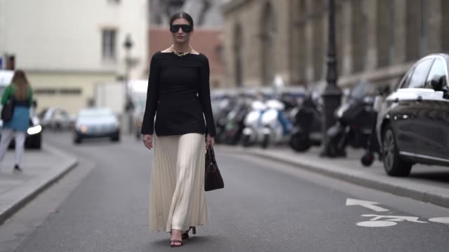 A guest wears a black top a white pleated skirt sunglasses outside Paul Joe during Paris Fashion Week Womenswear Fall/Winter 2019/2020 on March 03...