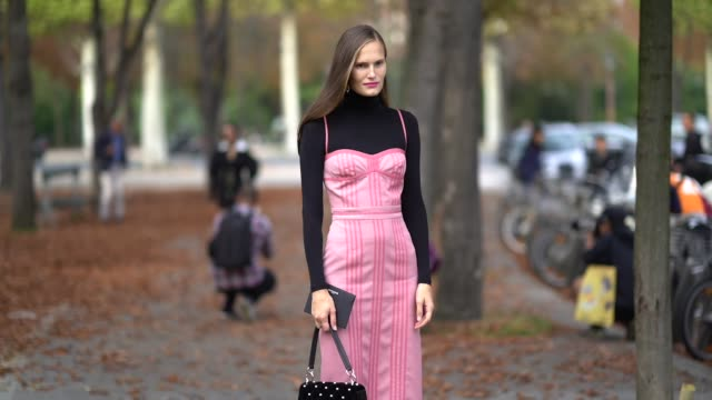 stockvideo's en b-roll-footage met a guest wears a black turtleneck top a pink striped strapless dress a black studded bag green velvet laceup platform shoes outside the rochas show... - coltrui