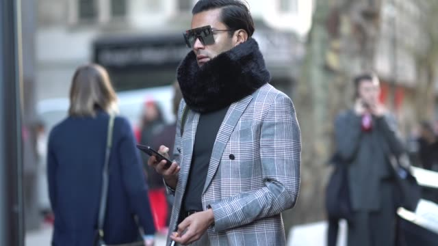 A guest wears a blazer jacket sunglasses a scarf during London Fashion Week Men's January 2018 on January 07 2018 in London England