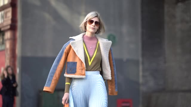 guest wears a blue and orange aviator jacket with sheep wool inner lining, a blue skirt, an orange bag, leather boots, a pink top, sunglasses, during... - fashion week stock videos & royalty-free footage