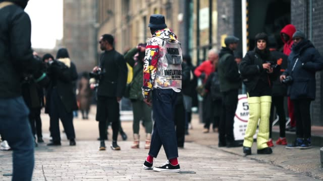 guest wears a blue bob hat, a michiko 'inflatable' plastic jacket, blue jeans, red socks, poses in front of photographers, during london fashion week... - jeans stock videos & royalty-free footage
