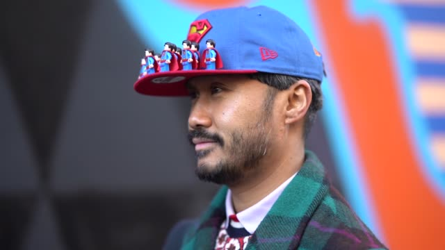 guest wears a blue cap with the superman logo, a green checked coat, yellow shoes with drawings, during london fashion week men's january 2018 on... - london fashion week点の映像素材/bロール