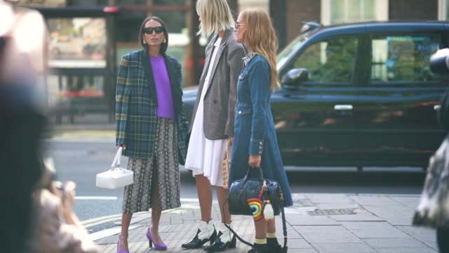 A guest wears a blue checked blazer jacket a purple top a black and white skirt purple shoes during London Fashion Week September 2018 on September...