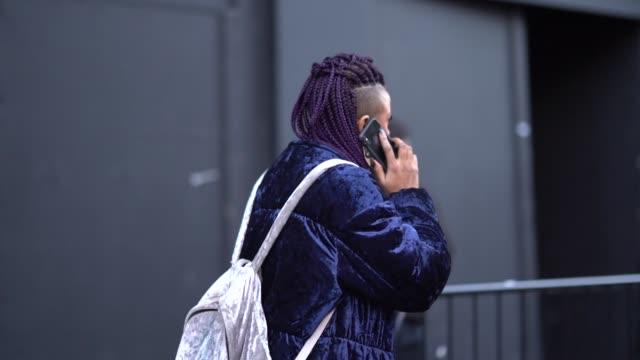 guest wears a blue coat, a backpack, print shoes, red sunglasses, has purple hair, during london fashion week men's january 2018 on january 07, 2018... - london fashion week点の映像素材/bロール