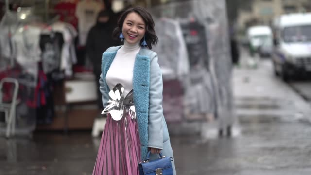 A guest wears a blue coat with wool inner lining a white turtleneck a pleated pink skirt a blue bag red heels shoes outside Elie Saab during Paris...