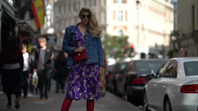 vidéos et rushes de a guest wears a blue denim jacket a red bag and a purple dress outside topshop during london fashion week september 2017 on september 17 2017 in... - semaine de la mode de londres
