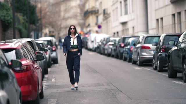 A guest wears a blue denim jacket blue jeans sunglasses a cropped green and white polo shirt outside Elie Saab during Paris Fashion Week Womenswear...