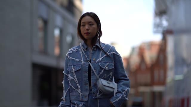 vídeos de stock e filmes b-roll de guest wears a blue denim jacket, flared pants, a blue semi circular bag, during london fashion week men's june 2018 on june 10, 2018 in london,... - jaqueta jeans