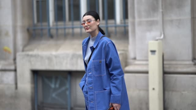 a guest wears a blue long denim jacket blue jeans black and white sneakers a gray wool top orange sunglasses outside acne studios during paris... - jeans stock videos & royalty-free footage