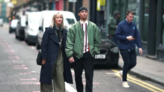 A guest wears a blue military jacket a guest wears a green bomber jacket during London Fashion Week Men's January 2019 on January 05 2019 in London...