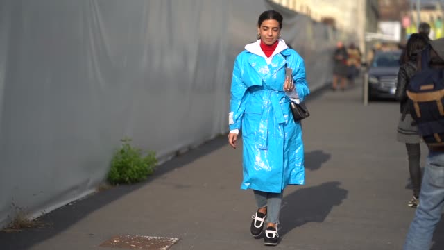 A guest wears a blue plastic coat during Milan Menswear Fashion week Fall/Winter 2018/19 on January 14 2018 in Milan Italy
