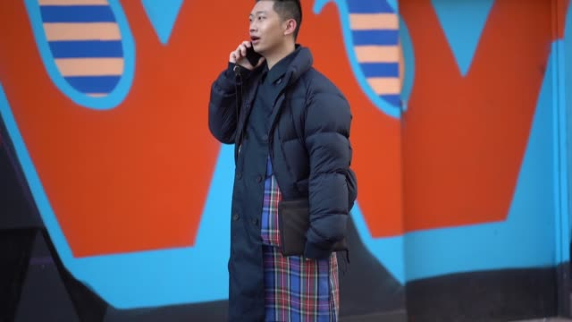 A guest wears a blue puffer coat a blue checked outfit a clutch white sneakers and is using a smartphone during London Fashion Week Men's January...