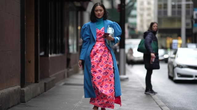 a guest wears a blue turtleneck pullover a blue long coat with puff sleeves a pale blue bottega veneta quilted bag a pink and purple floral print... - kleid stock-videos und b-roll-filmmaterial