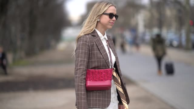A guest wears a brown blazer jacket sunglasses white dress brown boots a red bag outside Chanel during Paris Fashion Week Womenswear Fall/Winter...