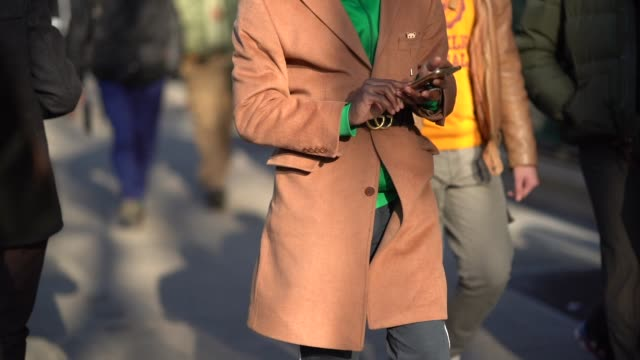 A guest wears a brown coat a Gucci belt a green sweater during Milan Menswear Fashion week Fall/Winter 2018/19 on January 13 2018 in Milan Italy