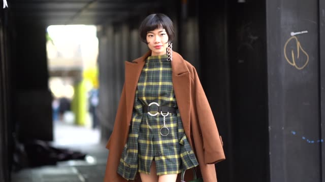guest wears a brown coat, a yellow and green checked dress, a green bag, flower print shoes, during london fashion week men's january 2018 on january... - london fashion week点の映像素材/bロール