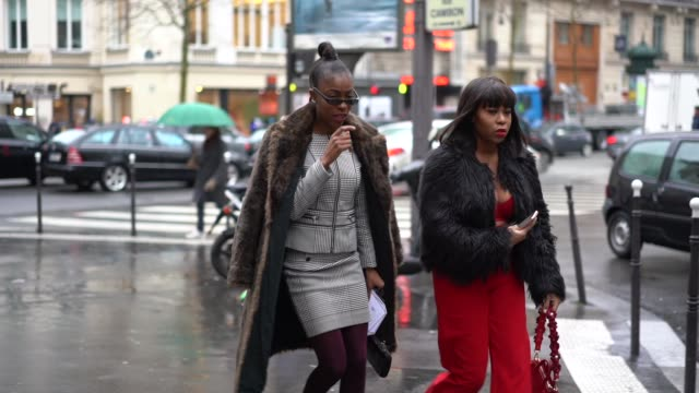 A guest wears a brown faux fur coat a gray checked dress purple tights a guest wears a black faux fur fluffy coat red flare pants a red bag during...