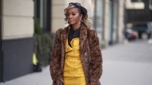 guest wears a brown fur fluffy coat, earrings, a black shirt, a yellow jacket, a chanel brooch, red leggings, floral print high boots, sunglasses,... - brown stock videos & royalty-free footage
