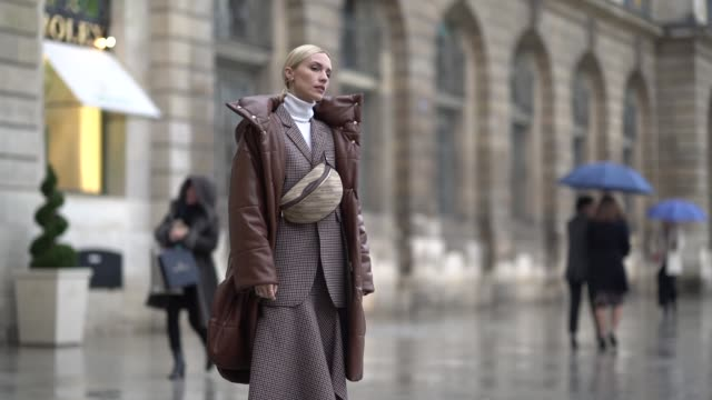 A guest wears a brown long puffer coat a Balenciaga fanny pack bag a checked blazer jacket a white turtleneck outside Alexis Mabille during Paris...