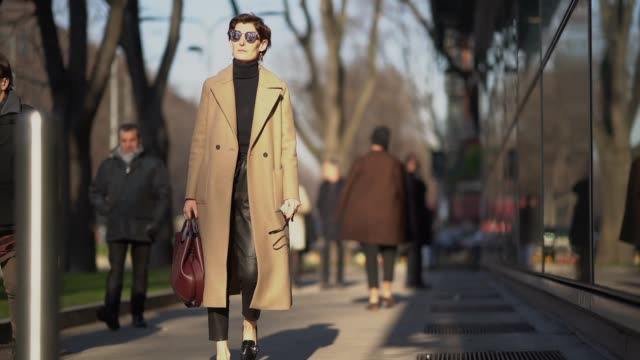 A guest wears a camel coat a purple bag sunglasses during Milan Menswear Fashion week Fall/Winter 2018/19 on January 13 2018 in Milan Italy