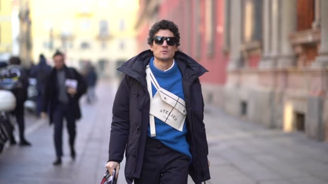 A guest wears a canada goose coat a blue top sunglasses an Atelier white bag during Milan Menswear Fashion week Fall/Winter 2018/19 on January 14...