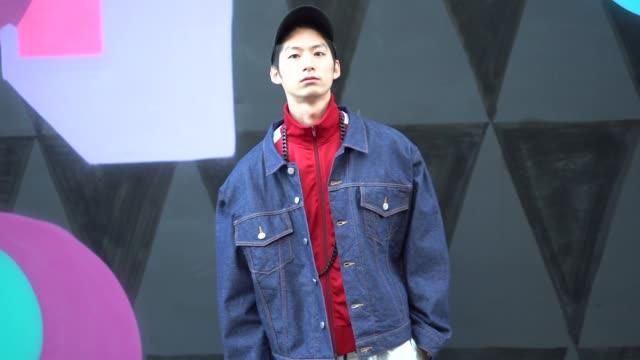 guest wears a cap, a red sportswear jacket, a blue denim jacket, silver pants, during london fashion week men's january 2018 on january 07, 2018 in... - london fashion week点の映像素材/bロール