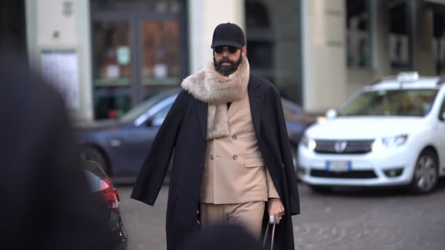 A guest wears a cap a scarf a dark coat a camel outfit during Milan Menswear Fashion week Fall/Winter 2018/19 on January 14 2018 in Milan Italy