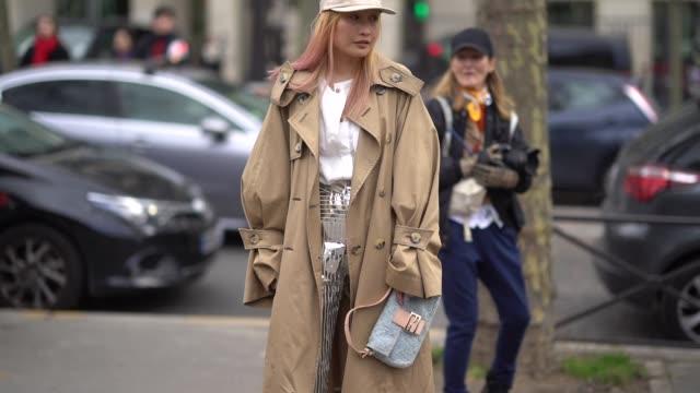 guest wears a cap, a trench coat, silver boots , outside miu miu, during paris fashion week womenswear fall/winter 2018/2019, on march 6, 2018 in... - トレンチコート点の映像素材/bロール