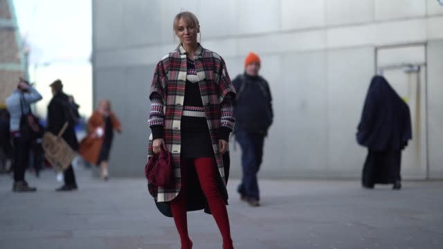 a guest wears a checked coat red thigh high boots during london fashion week february 2018 on february 17 2018 in london england - london fashion week stock videos and b-roll footage