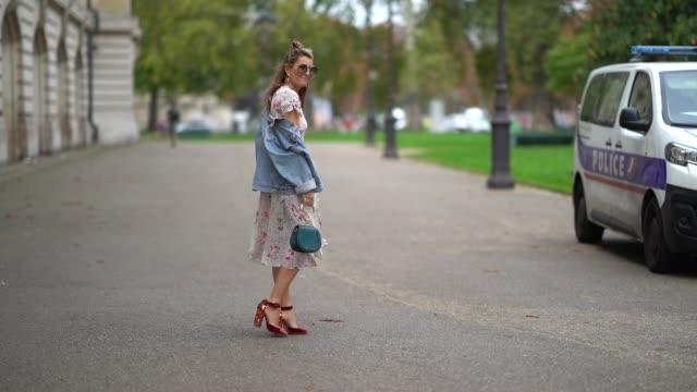 A guest wears a Chloe green bag a flower print dress blue denim jacket sunglasses outside Manish Arora during Paris Fashion Week Womenswear...
