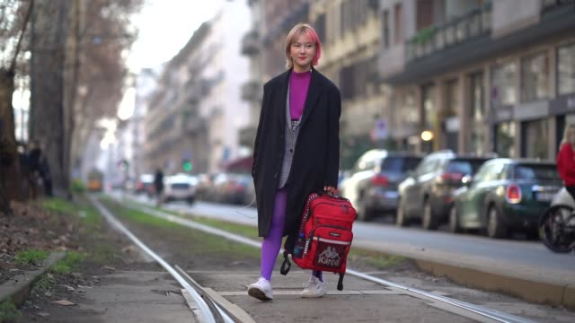 A guest wears a coat a red backpack purple leggings white sneakers during Milan Menswear Fashion week Fall/Winter 2018/19 on January 13 2018 in Milan...