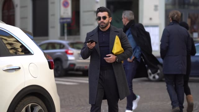 a guest wears a coat and a yellow clutch during milan menswear fashion week fall/winter 2018/19 on january 14 2018 in milan italy - borsetta video stock e b–roll