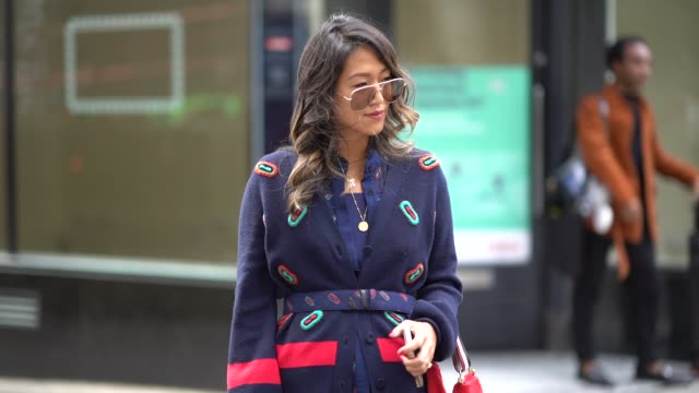 A guest wears a dark blue blazer jacket a red bag a blue pleated skirt with colored prints boots aviator sunglasses during London Fashion Week...
