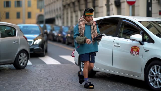 A guest wears a Fantasy beanie hat a checked scarf a blue pull over a short fur sandals during Milan Menswear Fashion week Fall/Winter 2018/19 on...