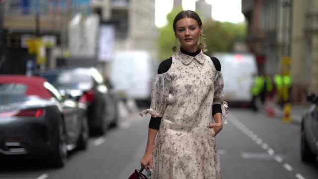 a guest wears a floral print dress a burgundy bag black shoes during london fashion week september 2018 on september 14 2018 in london england - floral pattern stock videos & royalty-free footage