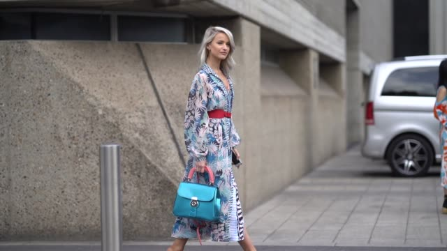 A guest wears a flower print dress a red belt a blue bag during London Fashion Week February 2018 on February 18 2018 in London England