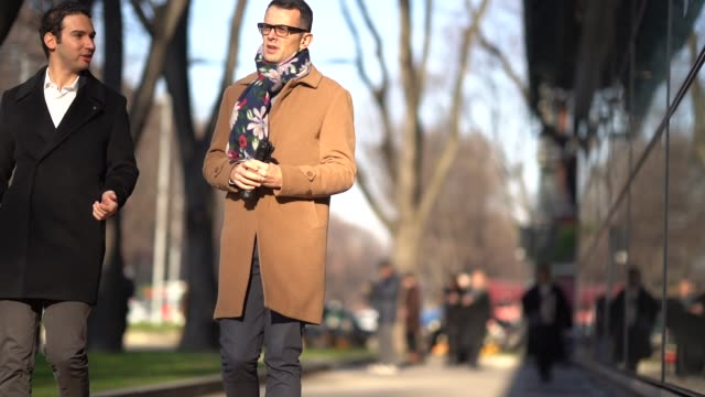 A guest wears a flower print scarf a camel coat during Milan Menswear Fashion week Fall/Winter 2018/19 on January 13 2018 in Milan Italy