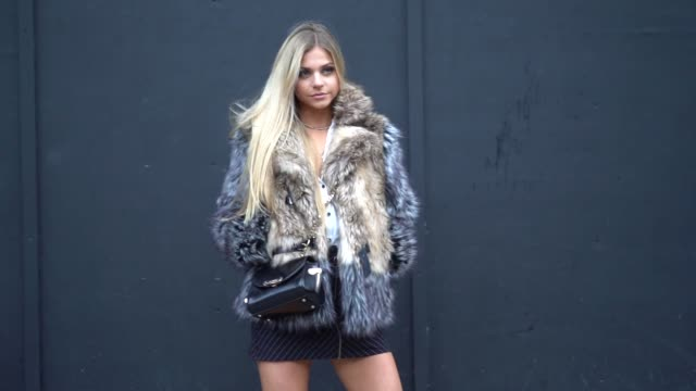 A guest wears a fur coat and a black bag during London Fashion Week Men's January 2018 at on January 06 2018 in London England
